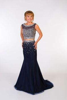 High neck beaded top with covered sweetheart neckline. The back of the top is open to mid-back, with a strap along the top of the shoulders. The fitted skirt has a beaded waistband with scattered beading to the knee where the skirt starts to softly kick out. Product Code: 0796 Colour: Navy
