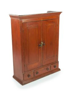 "TABLETOP CUPBOARD.  American, 19th century, pine. Red wash table top cupboard with three dovetailed drawers, brass turn keepers and hinges, and raised panel blind doors. Beaded case with three interior shelves. Square nailed as well. 42 7/8"" h. 34""w 13""d"