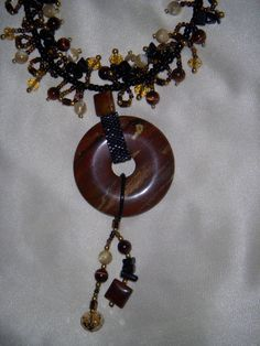 Agate donut with stitched accents.  Crystals, stones and seed beads.