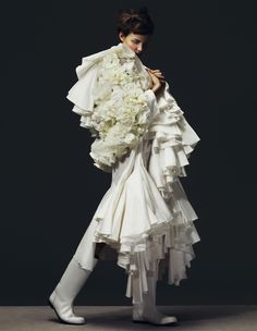 hat and all over white insp. clothes are layered on in unconventional way to expressed organized chaos