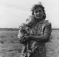On Arizona Highway 87, south of Chandler, Arizona. Grandmother and sick baby of migratory family camped in a trailer in an open field. They came from Amarillo, Texas, to pick cotton in Arizona.  Photo by Dorothea Lange,11/1940