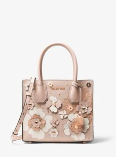 Crafted from pebbled leather with floral embellishments, this tactile accessory is a fresh take on our Mercer crossbody. Its streamlined design features structured top handles and a removable shoulder strap for added versatility, while a median zippered compartment promises safe-keeping for smaller items. Finished with a lock charm, this carryall combines signature style with a feminine spirit.