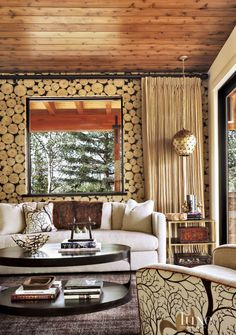 The wood-like Andrew Martin wallpaper and tree-patterned armchair and accent pillow allow this family room to walk the line between eclectic and country.