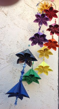 This order includes an origami kusudama flower mobile with 8 rainbow colored origami flowers. Each flower measures 3-1/2 inches wide and hangs gracefully from a 5 inch brass ring. A large yellow origami sun hangs from transparent line in the middle with rainbow beads and a glass crystal accentuating the entire mobile. Many rainbow colored beads decorate this origami rainbow mobile that hangs approximately 15 inches long. This origami mobile can be customized to your choice of colored…