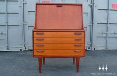 Mid century modern secretary desk in teak. Absolutely gorgeous solid construction throughout. Top door folds down to provide ample workspace, and reveals a removable shelf. In near mint original condition.    Measures: 35″ wide x 18″ deep x 50″ tall  Interior cabinet: 34″ wide x 9″ deep x 18.5″ tall