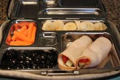 Turkey slices wrapped around cucumbers and cherry tomatoes, black olives, carrots and banana slices.