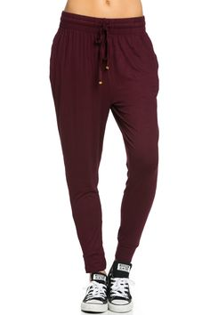 Super light weight burgundy jogger pants with adjustable drawstring and gold stopper detail. This super comfy jogger pants are perfect for indoors and out. Pair them with your favorite basic or graphi