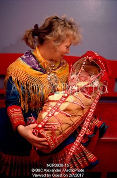 Image of sami mother with her baby in traditional cradle at christening. kautokeino, norway by ArcticPhoto barnehage