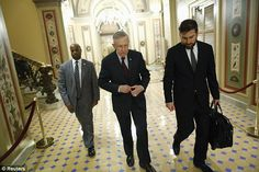 U.S. Senate Majority Leader Harry Reid (D-NV) (C) departs with an aide and his security detail after talks with the U.S. House of Representa...