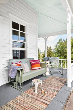 Despite the home's crusty exterior, all the expansive porch needed to take it from scary to airy was new flooring and a fresh coat of paint. Inspired by a superstition that a light blue ceiling would repel bees, Christina painted it a soft blue-green shade.