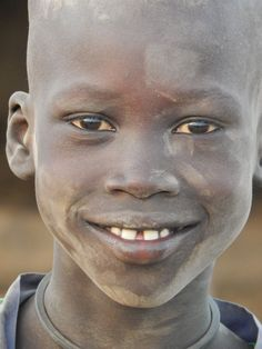 African boy smiles to fight off hunger.