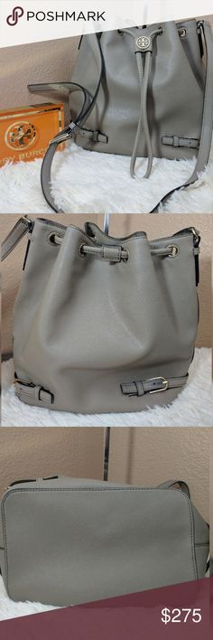 "Tory Burch Robinson Bucket Bag Grey Saffiano Mint condition except two very small makeup marks in bottom of interior.  Otherwise, new condition. Includes large non Tory dust bag.  9 ?""W x 10 ?""H x 6""D. (Interior capacity: small.)  18""-21 ?"" crossbody strap drop  Belt details and goldtone logo hardware add everyday sophistication to a lightly structured bucket bag done up in richly textured Saffiano leather.  Drawstring closure.  Adjustable crossbody strap.  Interior zip, wall and smartphone…"