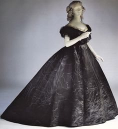Mourning dress of black watered silk for evening, circa 1861.The neck and sleeves are trimmed with lace and jet. This dress followed regulations issued for General Mourning for death of Prince Albert.  Via Antique & Vintage Dress Gallery.