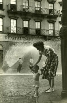 Mother and baby in gutter. New York, undated. By Ruth Orkin The force of the hydrant back when this pic was taken was tremendous - good thing Mom has a handle on it