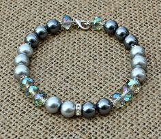 Silver Faux Pearl & Crystal Memory Wire Bracelet $10.00 This+beautiful+bracelet+is+made+with+gray+and+silver+faux+pearls,+clear+ab+faceted+rondelle+crystals,+silver+daisy+spacers+and+a+silver+plated+rhinestone+spacer+focal+with+a+silver+plated+lobster+clasp.++Let+us+know+your+wrist+size+upon+ordering+to+ensure+a+proper+fit.+
