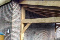 Een robuuste eikenhouten afdak met oudhollandse dakpannen. De houtconstructie is verouderd om heteen extra oude look te geven.