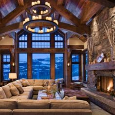 Love the idea of a huge sectional like that in front of a fireplace. Also love the huge windows