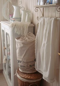 Delicate French farmhouse bathroom with lovely white linens, a whicker basket and vintage pitchers.