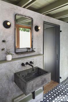 The new casita bathroom features a custom concrete sink, plaster walls, and custom concrete tile.