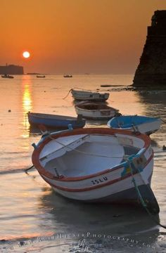 Romantic vacation scene with small wooden fishing boats during a colorful sunset in Cadiz, Spain.