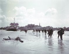6 June 1944: Troops of the 3rd Canadian Infantry Division land at Juno Beach on the outskirts of Bernières-sur-Mer on D-day. 5 May 2014: A view of the seafront and beach in Normandy today. 340 Canadian soldiers lost their lives in the battle for the beachhead. Photographs by Galerie Bilderwelt/Getty and Peter Macdiarmid/Getty
