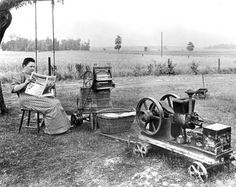 Somewhere in the American Midwest, a woman sits and reads the newspaper, while waiting for her gas powered washing machine to finish a load ...