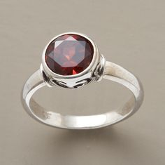 """A deep red, faceted garnet flashes and flirts from an ornately scrolled sterling silver setting. Whole and half sizes 5 to 9-1/2. Approx. 1/16""""W."""