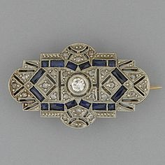 An Art Deco sapphire and diamond panel brooch The central brilliant-cut diamond within an openwork geometric frame of rose diamonds and calibré synthetic sapphires, 3.0 x 2.0cm, cased.