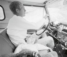 Steve McQueen driving his Land Rover, while his daughter, Terry, takes a nap.