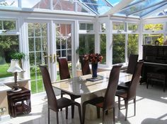 Picking Up the Best Conservatory Ideas to Make One for Yourself: Appealing Conservatory Interiors Dining Room Decoration With Elegant Furniture Table And Brown Chairs Also Flowers On Vase Ornament ~ workdon.com Architecture Inspiration