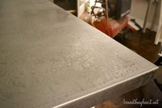 "Aged Zinc Table Top: galvanized sheet metal a 4 ft x 10 ft piece cost about $50. To turn edges 2"" took to a steel company, cost less than $100 to do. Mucuric acid to age, and wax paste finish.:"