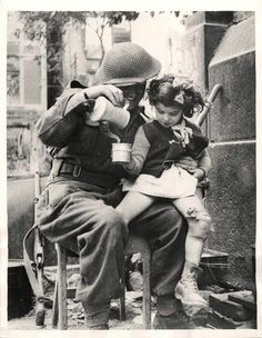 A British soldier gives soup to a little French girl in Caen (er is nog een foto met dezelfde soldaat en meisje: British soldier carries a little French girl through bombed ruins of Caen).