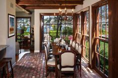 Stunning ocean views are the highlight of this airy Mediterranean-style dining room. A long wood table, big enough for 10, creates the ideal place to gather with friends and family. The large windows, rustic ceiling beams, brick floors and bright white walls offer plenty of style in the well-lit space.