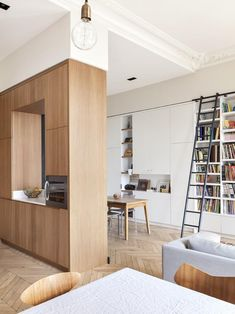 Family room with custom built-in bookshelves and rolling ladder in Paris apartment.