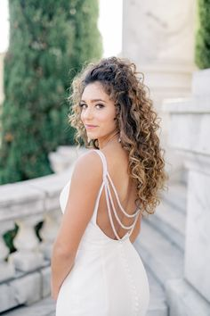 We custom draped our small sparkle straps along the back of Jade's sexy wedding dress for added detail. She is wearing our Tiffany Nicole spaghetti strap wedding dress, which features a low back and plunging neckline. #wedding #weddingdress #sexyweddingdress #customweddingdress #designerweddingdress #bride #bridalgown