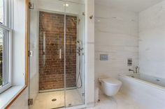 gorgeous bathroom with exposed brick in the shower