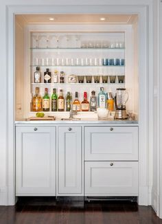 interior design bar cocktail butlers pantry with white cupboard doors and glass shelves with blender, cocktail shaker, glassware, chopping board, gin,rum, whiskey, ice (dp)