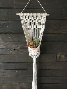 Macrame wall plant hanger up for grabs! I love these boho inspired pieces. They make a perfect addition to any room of your home. << Details >> Hanger crafted using 5 mm 100% cotton rope Hangs from wooden dial rod Width 12 Length: Roughly 40 Hanger is made to hold potted plants 4-6