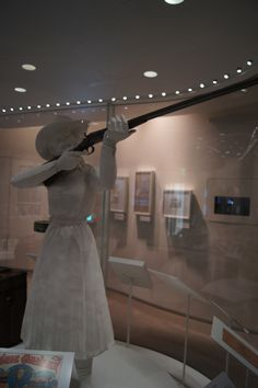 """Life size statue of Annie Oakley holding her actual gun on display in the National Cowgirl Museum and Hall of Fame's """"Hitting the Mark: Cowgirls and Wild West Shows"""" gallery."""