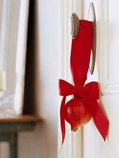 Deck the Door:   For a simple door decoration, hang a juicy red pomegranate from ribbon. Create a hanging loop by pushing the ends of a short length of florist's wire into the pomegranate. Thread red ribbon through the loop and tie in a bow at the top of the fruit.