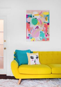 yellow couch with abstract artwork and colorful pillows with face