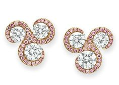 A PAIR OF DIAMOND AND COLORED DIAMOND EAR CLIPS.   Each set with three circular-cut diamonds, weighing from approximately 1.66 to 1.00 carat, within a circular-cut pink diamond surround, mounted in platinum and pink gold