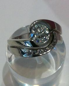 Bridal set in white gold with a swirl style 1.00ct. diamond set in a by-pass design with a custom wedding ring to snug including graduated diamond melee.