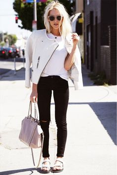A white t-shirt is paired with a white jacket, black skinny jeans, white sandals, and a pink bag