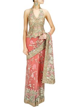 This designer Saree is featuring in a powder pink net with gold thread floral embroidery. This designer saree comes along with gold fully zardozi embroidered halter neck designer blouse and pink gold