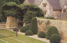 Classic english country house - looks like Cotswold stone to me, wonderful with the topiary around the tennis court.