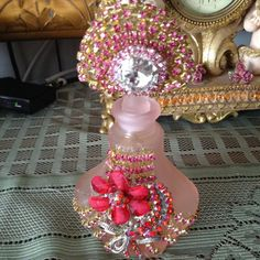 Pink frosted perfume bottle with frosted front and sides Stoppe has fan shaped rhinestone accessories with a jewel. The base of the bottle has