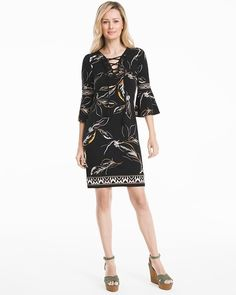 """A combination of florals and lace-up front transform a simple chemise dress into a walking work of art. Pair with sandals or wedges.   Black with canary floral print shift dress Lace-up V-neck with tassel ends  Three-quarter bell sleeves Soft goldtone hardware Approx. 36"""" from shoulder; hits above the knee  Polyester/spandex. Machine wash cold.  Imported"""