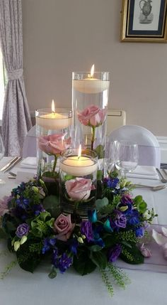 Ring of flowers around cylinder vases with floating candles