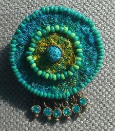 Pin de textil Bobo, etno, Chic elegante. Verde Veronés Original joya en un círculo de fieltro cubierto con fragmentos de saris Roca India y seis turquesa bolas. Textil diseño azul/verde y verde/amarillo. Tamaño: 3, 5 x 4, 5cm.